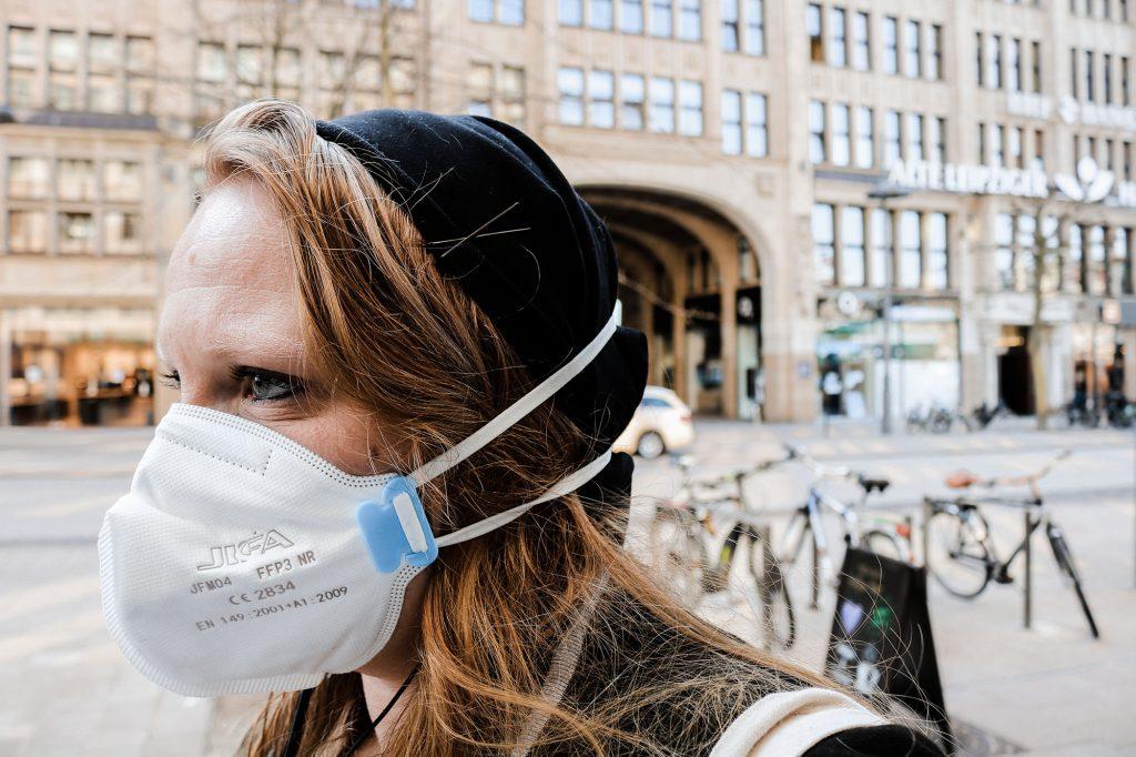 Seitenansicht einer jungen Frau mit langen, rotblonden Haaren, schwarzer Mütze und FFP3 Maske. Im hintergrund verschwommen helle Häuser und Fahrräder