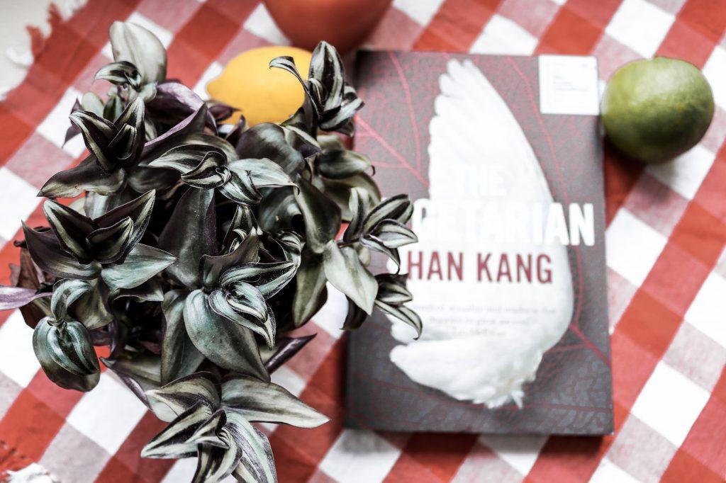 """Von oben fotografierte Pflanze mit grün-lila Blättern, im Hintergrund unscharf das Buch """"The Vegetarian"""" von Han Kang sowie eine Zitrone und eine Limette"""